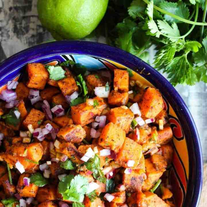 Colorful bowl of sweet potato salad with a lime and a bunch of cilantro.