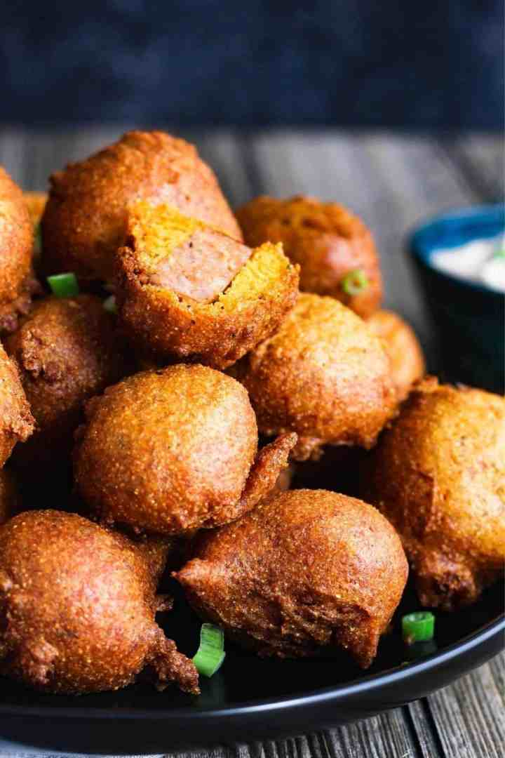 Stack of corn dog bites on a plate.