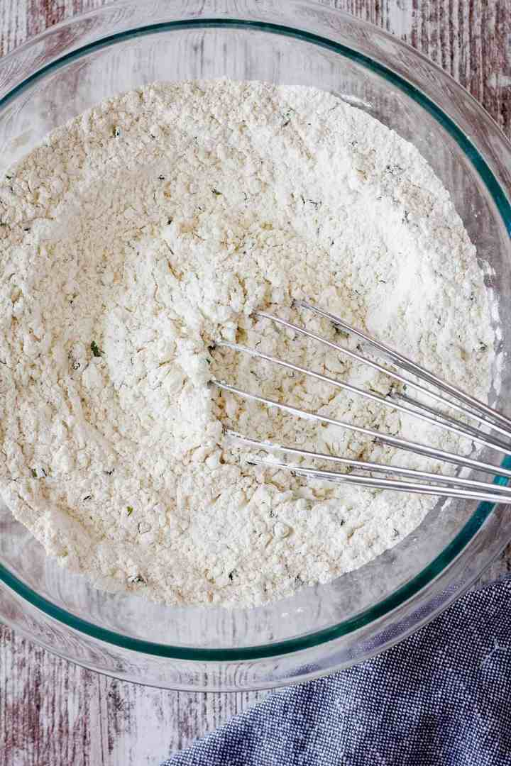 Combined dry ingredients in a bowl with a whisk.