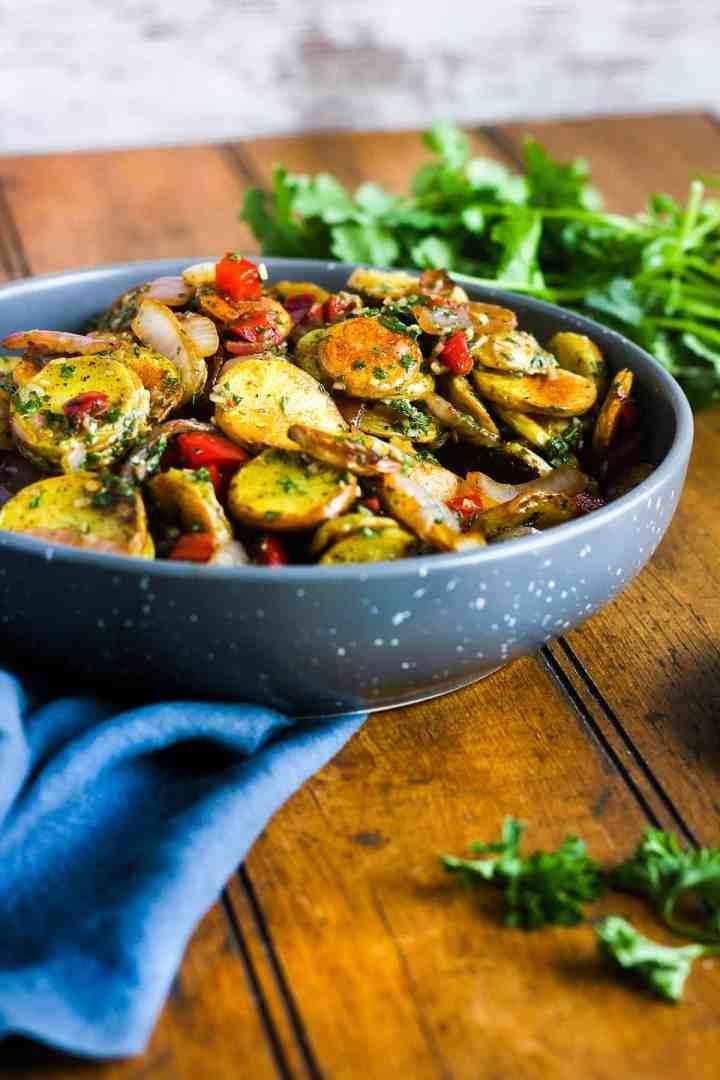 Bowl of vegan potato salad with fresh herbs.