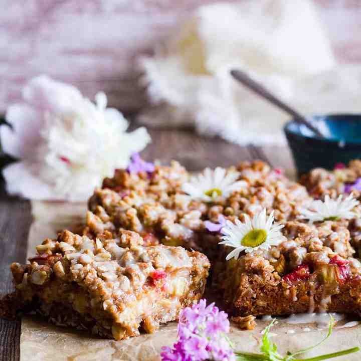 Rhubarb oatmeal bars with flowers and a bowl of glaze.