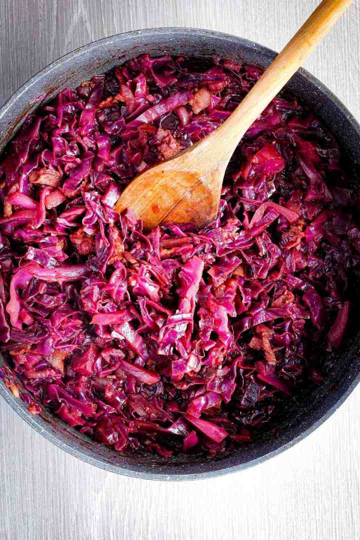 Braised cabbage with wooden spoon in pan.