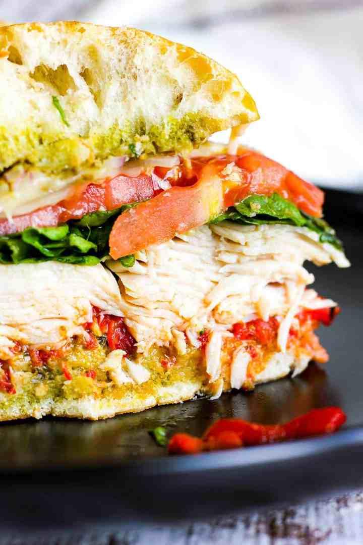 Close-up of turkey pesto sandwich cut in half.