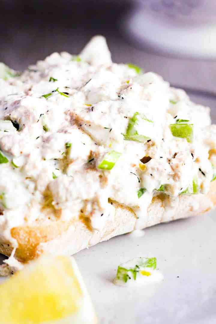 Close-up of lemon tuna salad with dill on a piece of bread.