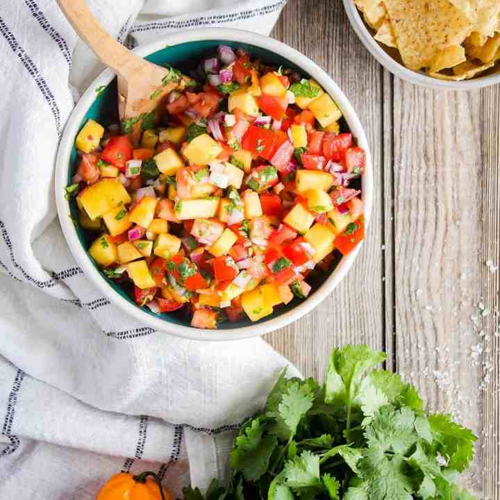 Bowl of fresh peach salsa with a bowl of chips and fresh produce.