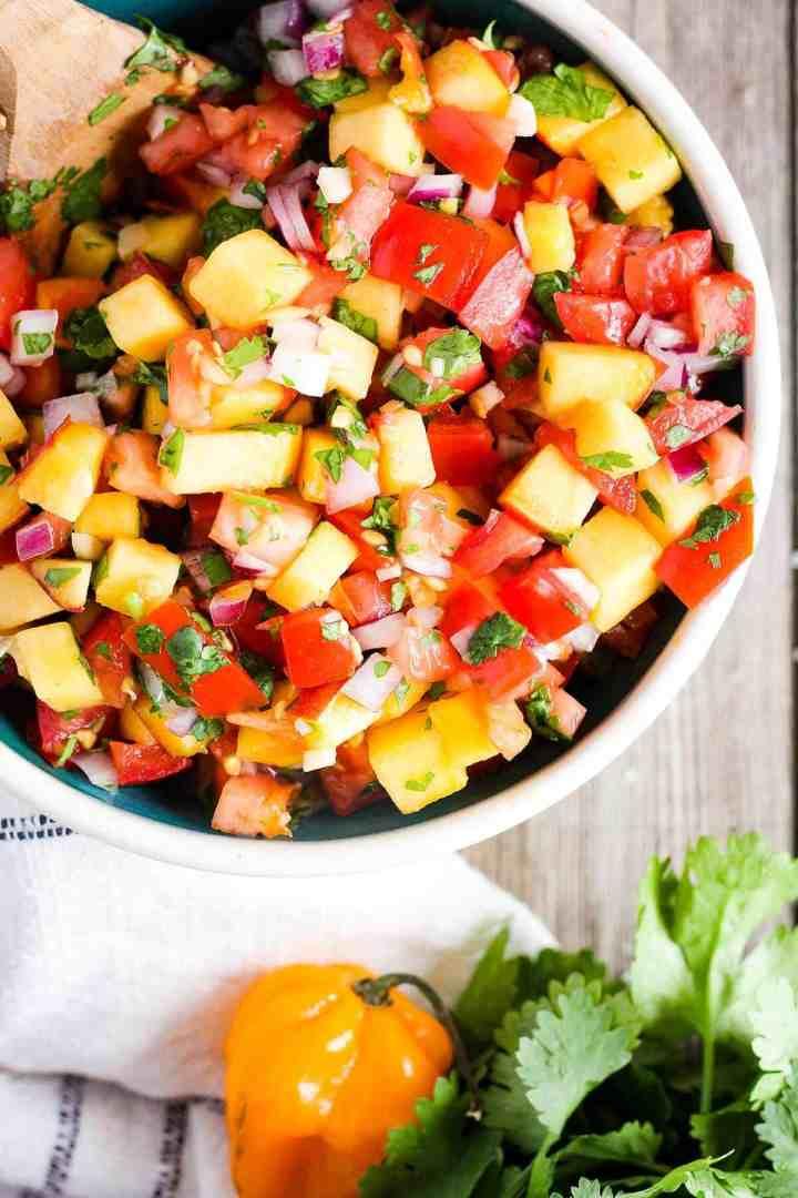Bowl of habanero peach salsa with a towel, a habanero, and cilantro.