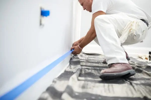 Painter removing painter's tape from baseboard.