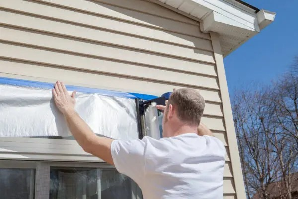 Man applying tape to home with vinyl siding.