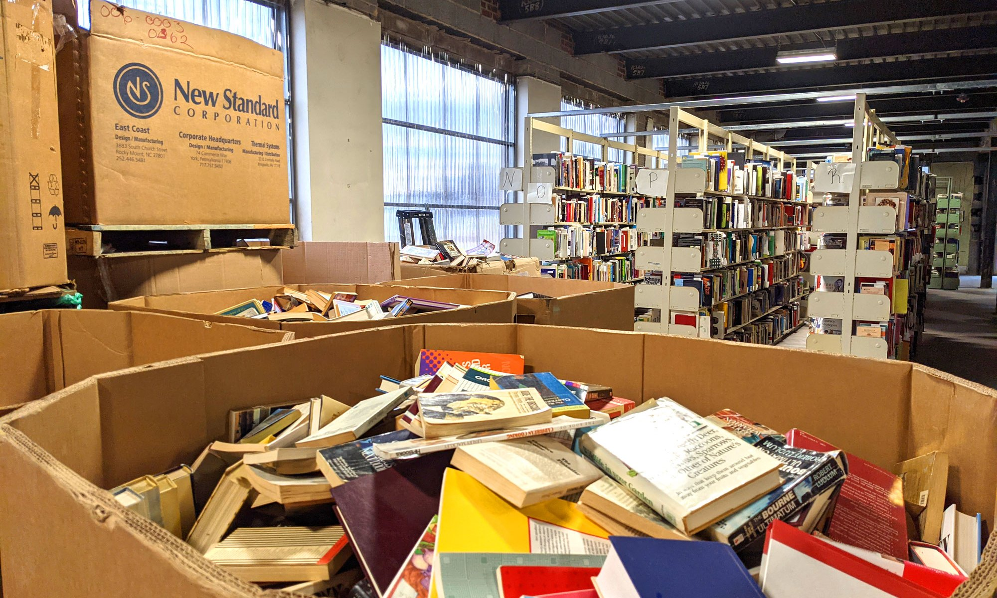 Warehouse with books inside of a large cardboard container and also on industrial shelving