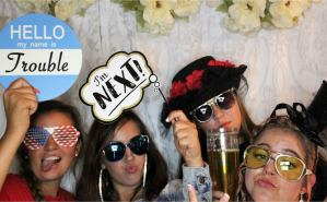 Group of friends having fun in photo booth