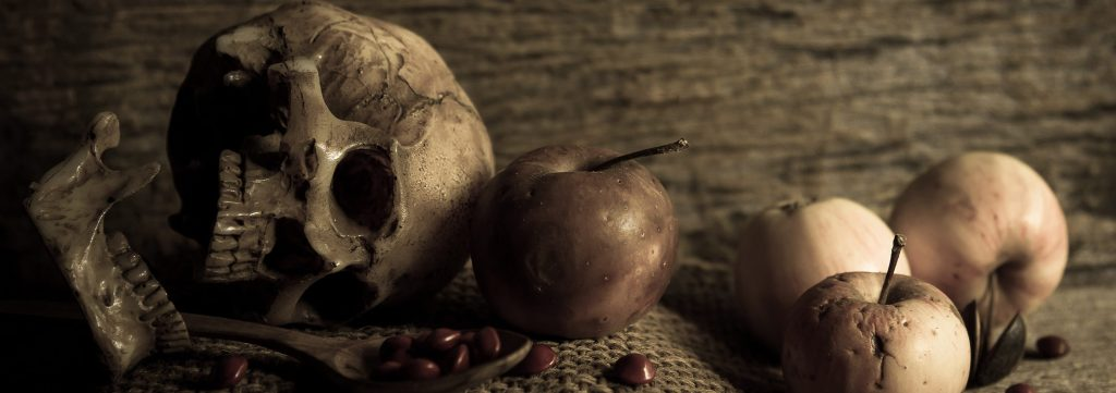 Skulls with rotten apples and a spoon of pomegranate seeds