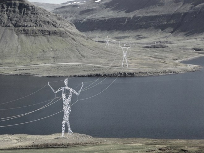 powerlines with transmission towers that look like giant abstract people holding the powerlines up over the landscape