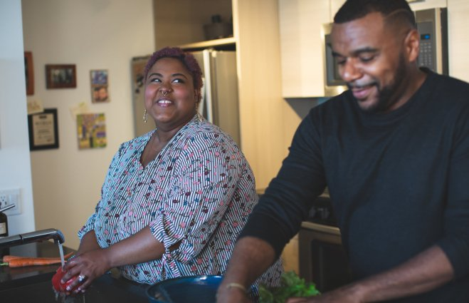 Black plus sized woman is washing a red pepper while smiling at her male partner