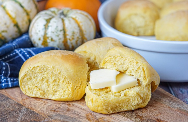 Three Pumpkin Yeast Rolls on a wooden platter with pumpkins in the background. The front yeast roll is split in half and filled with two slices of butter.