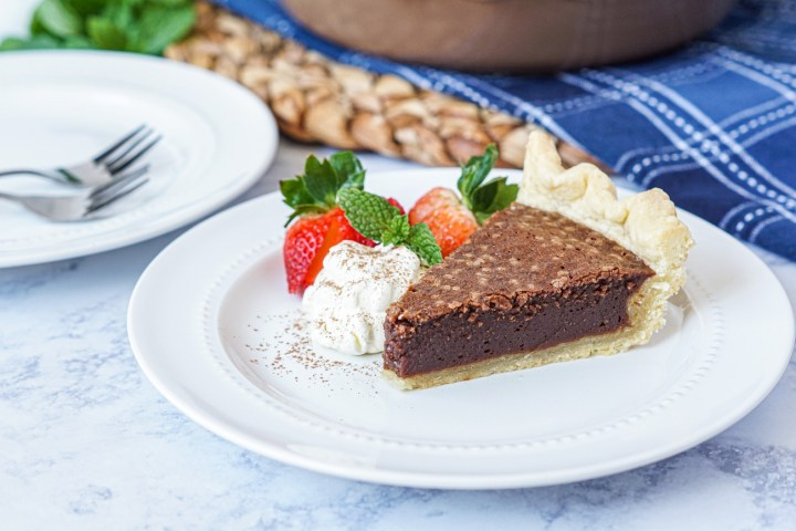 Slice of Chocolate Fudge Pie on a white plate next to whipped cream and two strawberries.