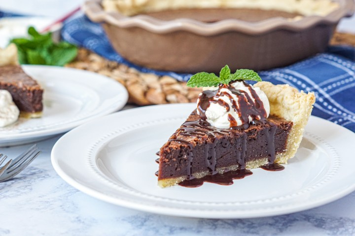 A slice of Chocolate Fudge Pie on a white plate and topped with whipped cream and a drizzle of chocolate sauce.
