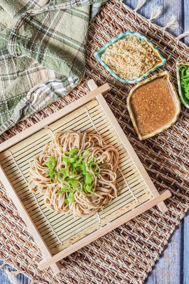 Aerial view of Kurumi Soba (Soba with Walnut Dipping Sauce) on a square board next to dipping sauce, ground walnuts, and green onions in small leaf bowls.