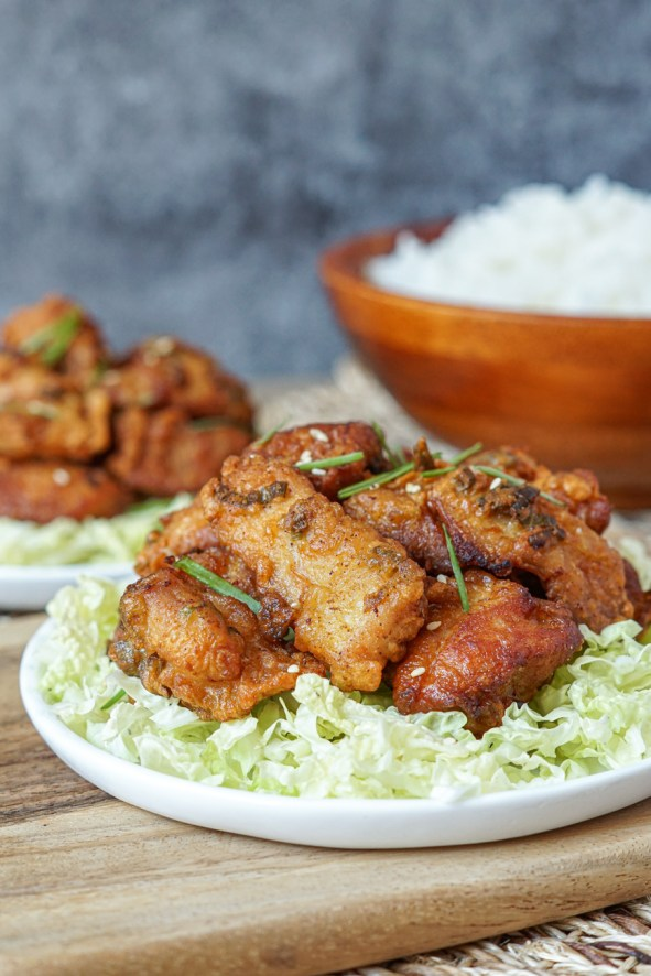 Side view of Mochiko Chicken on a white plate with shredded cabbage and a bowl of rice in the background.