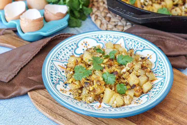 Batata Wa Bayd (Lebanese Potatoes and Eggs) on a white and blue plate with cracked eggs and cilantro in the background.