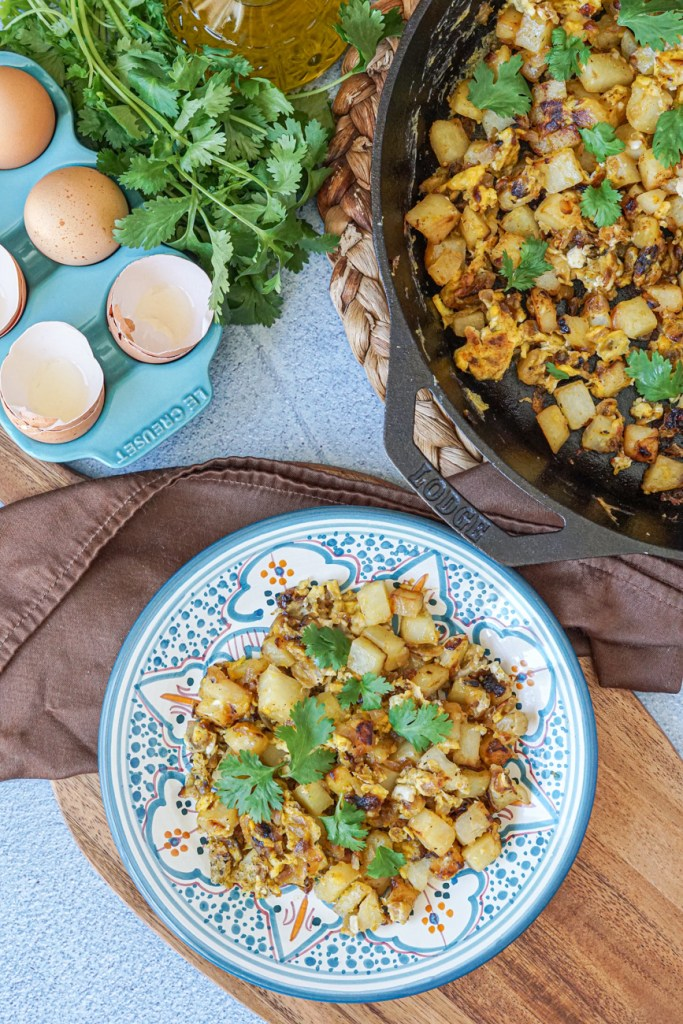 Aerial view of Batata Wa Bayd (Lebanese Potatoes and Eggs) on a white and blue plate next to more in a cast iron skillet and eggs in a blue container.