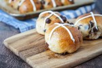 Three Chocolate Chip Hot Cross Buns on a wooden board.