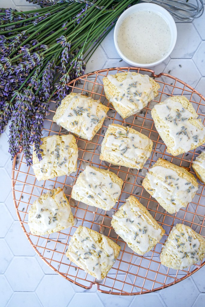 Aerial view of Lavender Vanilla Scones on a copper round rack next to lavender flowers and vanilla glaze.