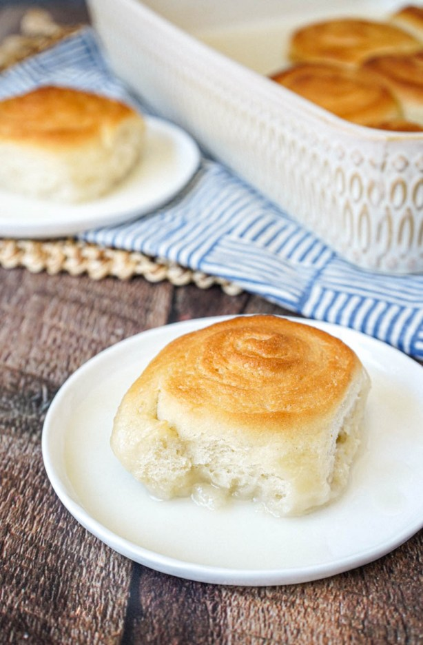 Pani Popo (Samoan Sweet Coconut Buns) on two white plates and in a baking dish.