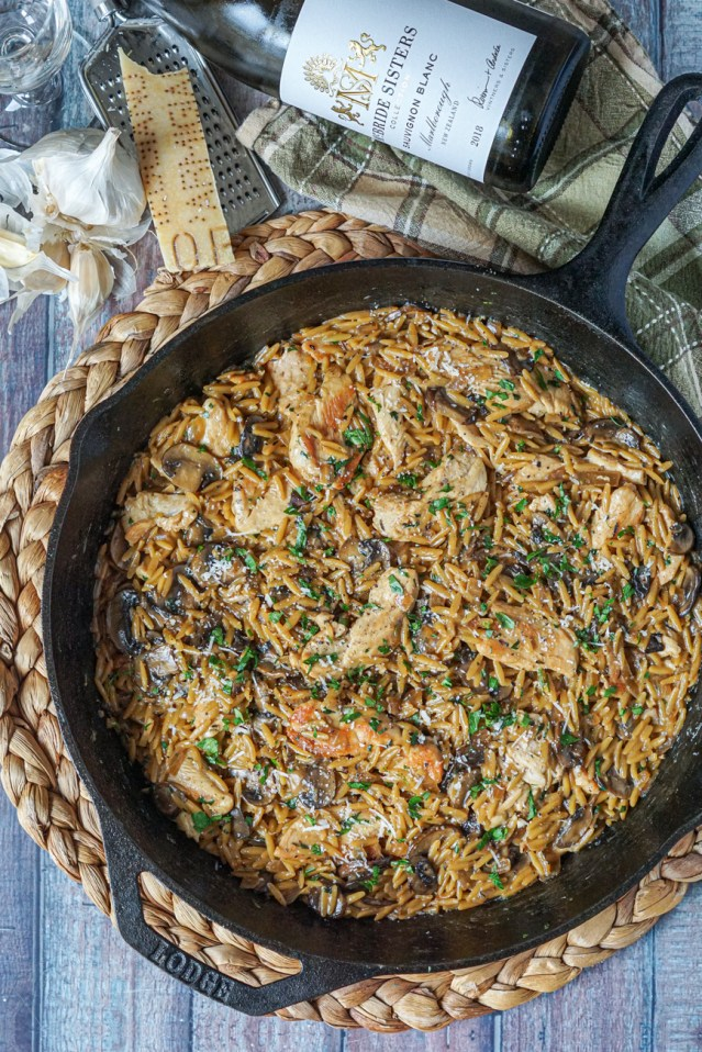 Aerial view of Chicken and Mushroom Orzo in a cast iron pan next to garlic, parmesan, and a wine bottle.