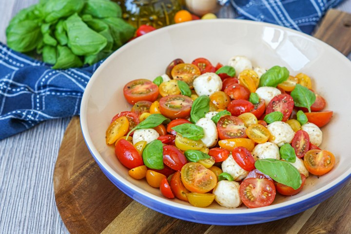 Cherry Tomato Mozzarella Salad in a large blue bowl on a wooden board.