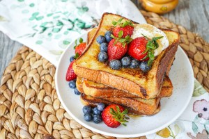 A stack of Vanilla Honey French Toast with strawberries and blueberries.