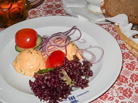 Obatzda from the Hofbräuhaus in Munich, Germany- on a white plate with lettuce, tomato, red onion, and cucumber.