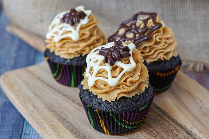 Three Brownie Cupcakes with Peanut Butter Frosting on a wooden board and topped with white and dark chocolate spiderwebs and spiders.