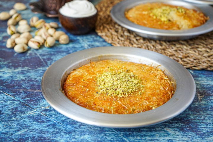 Künefe (Turkish Sweet Cheese Pastry) in two metal pans and topped with pistachios.