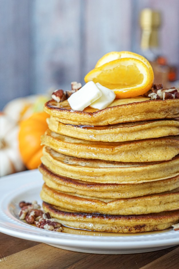 A stack of seven Orange Pumpkin Pancakes on a white plate and topped with orange slices.