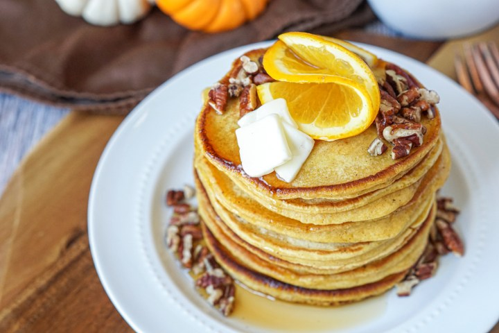 A stack of Orange Pumpkin Pancakes on a white plate and topped with orange slices and chopped pecans.