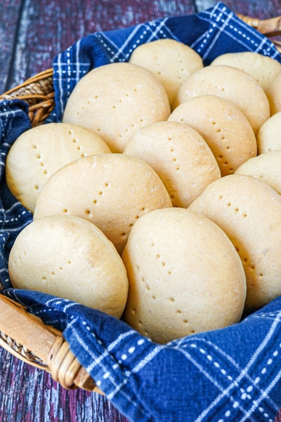 Aerial view of Pan Amasado (Chilean Kneaded Bread) lined up in a basket with a blue towel.
