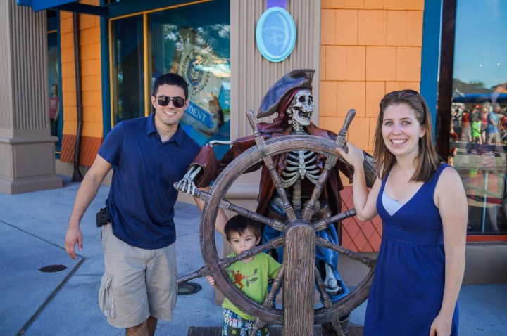 Mom, dad, and son standing next to steering wheel statue with skeleton pirate.