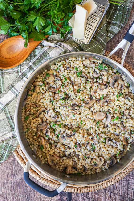 Aerial view of Pearl Couscous with Mushrooms in a pan next to a spoon and parsley.
