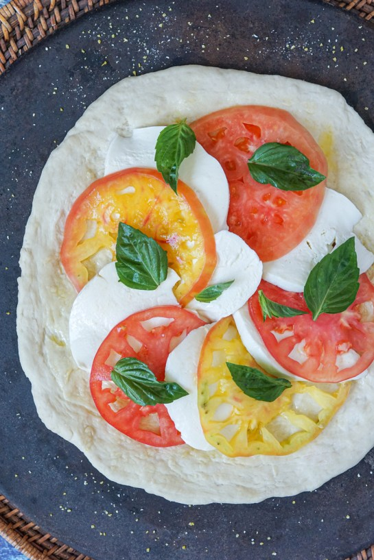 Assembling the Caprese Pizza on a pizza stone with alternating slices of tomato and mozzarella and fresh basil leaves.