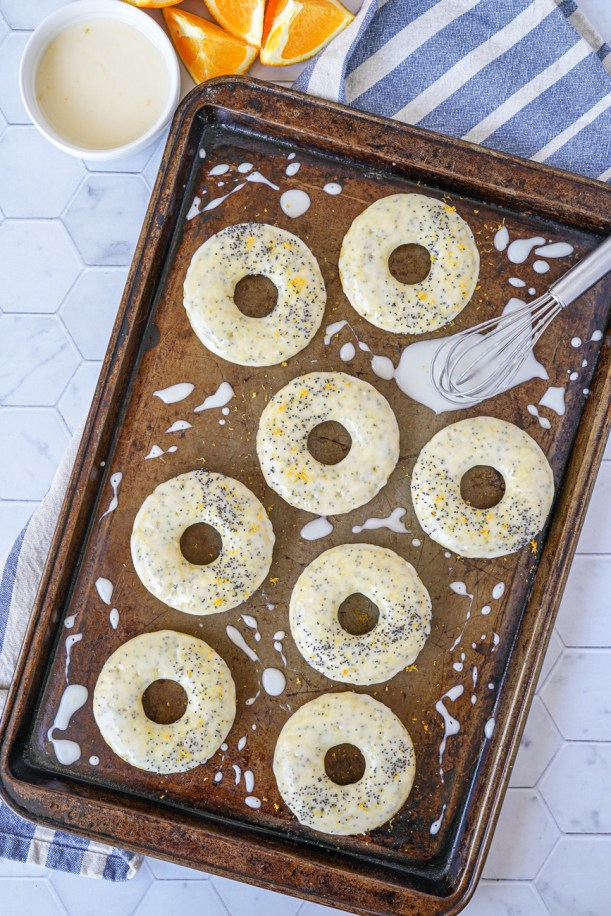 Aerial view of Orange Poppy Seed Baked Doughnuts on a baking sheet.