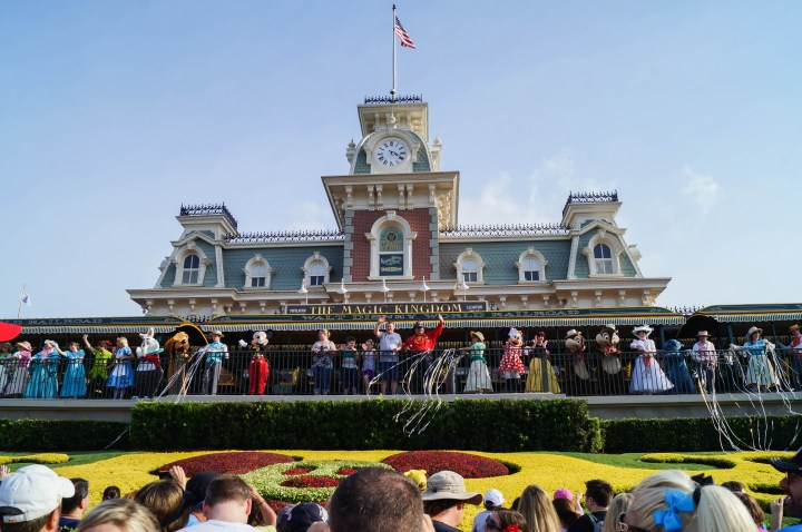 Entrance to Magic Kingdom with Characters lined up outside the train station to greet guests entering the park.