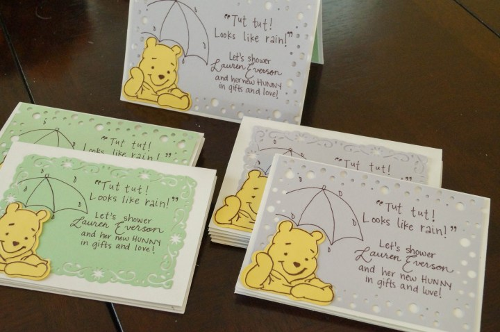 Five Winnie the Pooh Invitations on a table with purple and green paper.