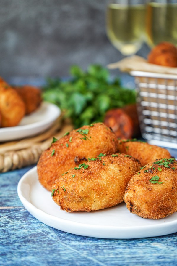 Side view of Croquetas de Chorizo on a white plate and topped with pieces of chopped parsley.