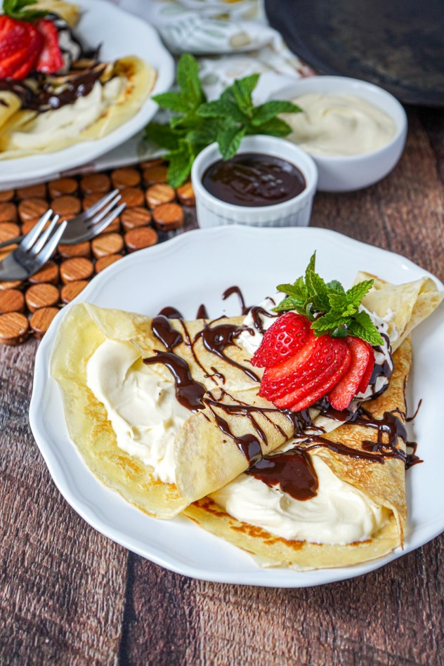 Mascarpone Crepes with Coffee Syrup on white plates small bowls of mascarpone and syrup.