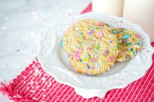 Three Sprinkle Sugar Cookies on a small white pedestal.