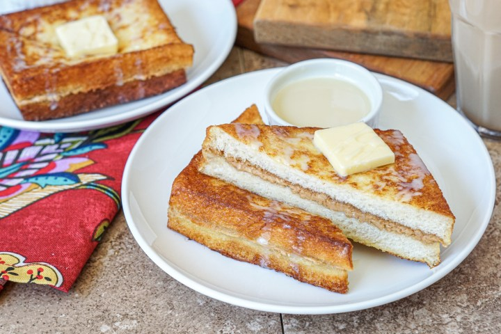 Hong Kong Style French Toast on two white plates drizzled with sweetened condensed milk and topped with a slice of butter.