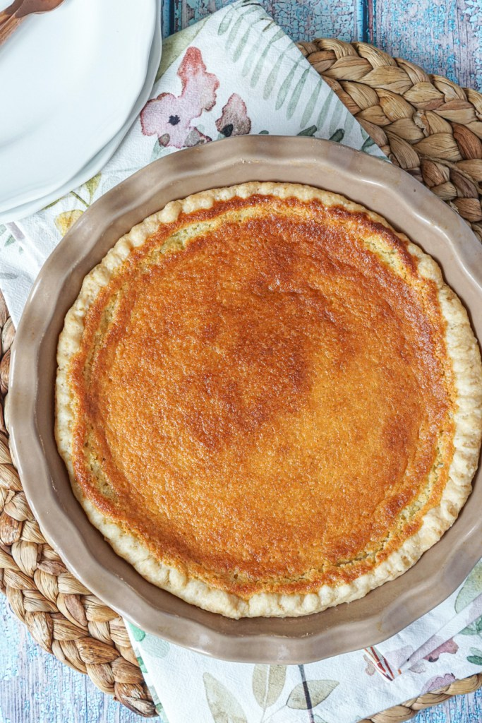 Aerial view of Vanilla Bean Buttermilk Pie in a tan pie dish.