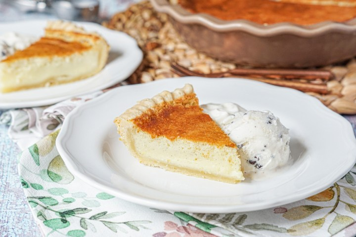 Slices of Vanilla Bean Buttermilk Pie on two white plates with ice cream and whipped cream.