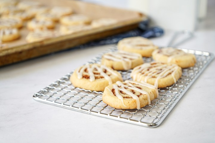 Six Cinnamon Roll Cookies on a wire rack with more in the background on a baking sheet.