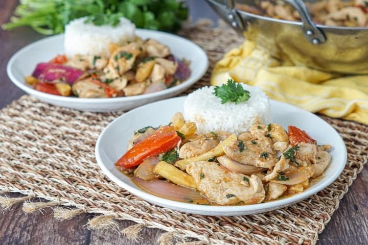 Pollo Saltado (Peruvian Chicken Stir-Fry) with rice and cilantro on two white plates.
